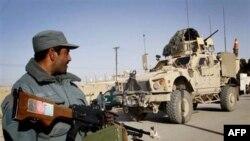 Cảnh sát Afghanistan canh gác bên cạnh một chiếc xe bọc thép của quân đội Mỹ gần hiện trường một vụ nổ bom xe hơi ở Kandahar, ngày 4/2/2011
