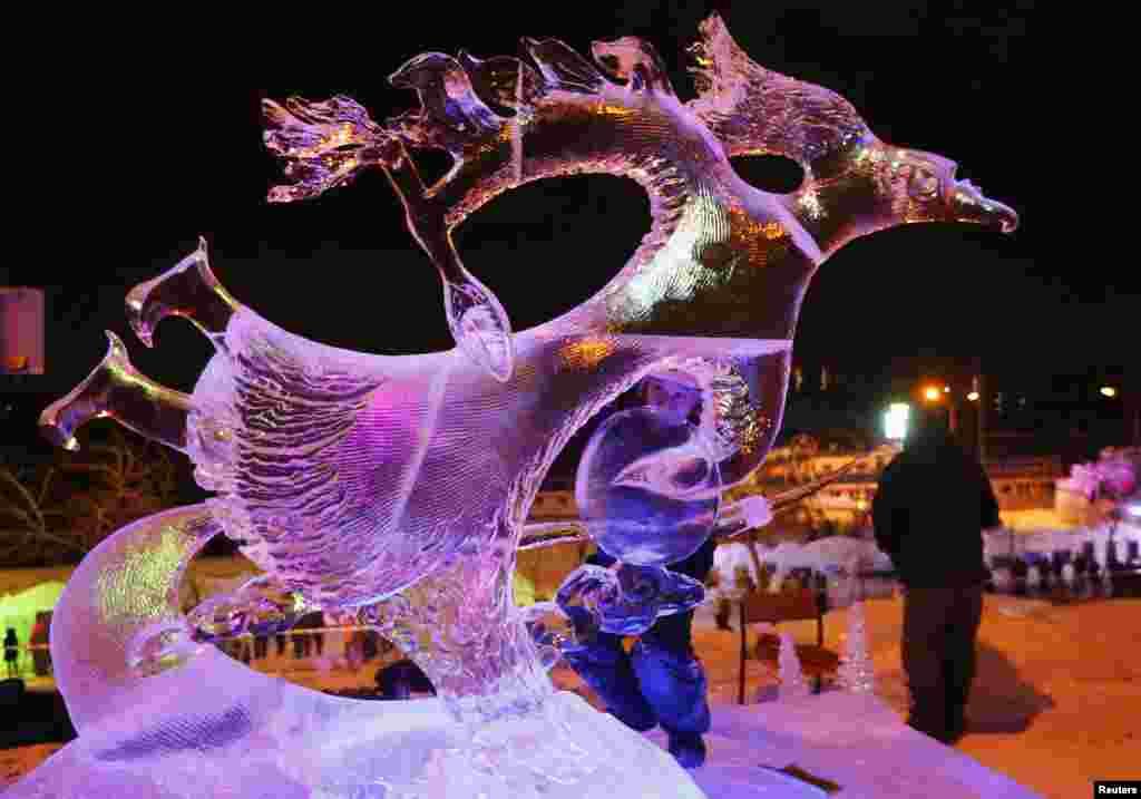 """Alexander Baranmaa menyelesaikan patung es """"Macro Space"""" pada festival es internasional di Krasnoyarsk, Siberia."""
