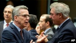 German Interior Minister Thomas de Maiziere, left, speaks with Luxembourg's Foreign Minister Jean Asselborn, right, during a meeting of EU justice ministers at the EU Council building in Brussels, March 10, 2016.