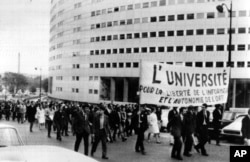 FILE - Paris students march on June 9, 1968, around the French Maison de la Radio in support of the striking TV and radio employees. The banner reads The University for the Liberty of News and the Autonomy of the ORTF (the Government controlled TV and radio system). Daily marches have been organized around the Radio House during the strike.