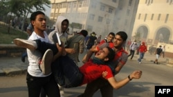 Student supporters of ousted president Mohamed Morsi carry a comrade injured during clashes with Egyptian security forces outside Al-Azhar university in Cairo on October 28, 2013.