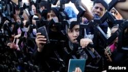 Warga Palestina berdesak-desakkan di belakang gerbang perbatasan Rafah, memegang paspor mereka untuk mencoba menyeberang ke Mesir dari Jalur Gaza (10/7).
