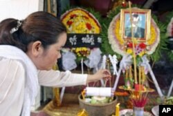 Sam Chanthy, wife of Chut Wutty, lights incense during Wutty's funeral at his house in Kandal province, Cambodia, April 28, 2012.