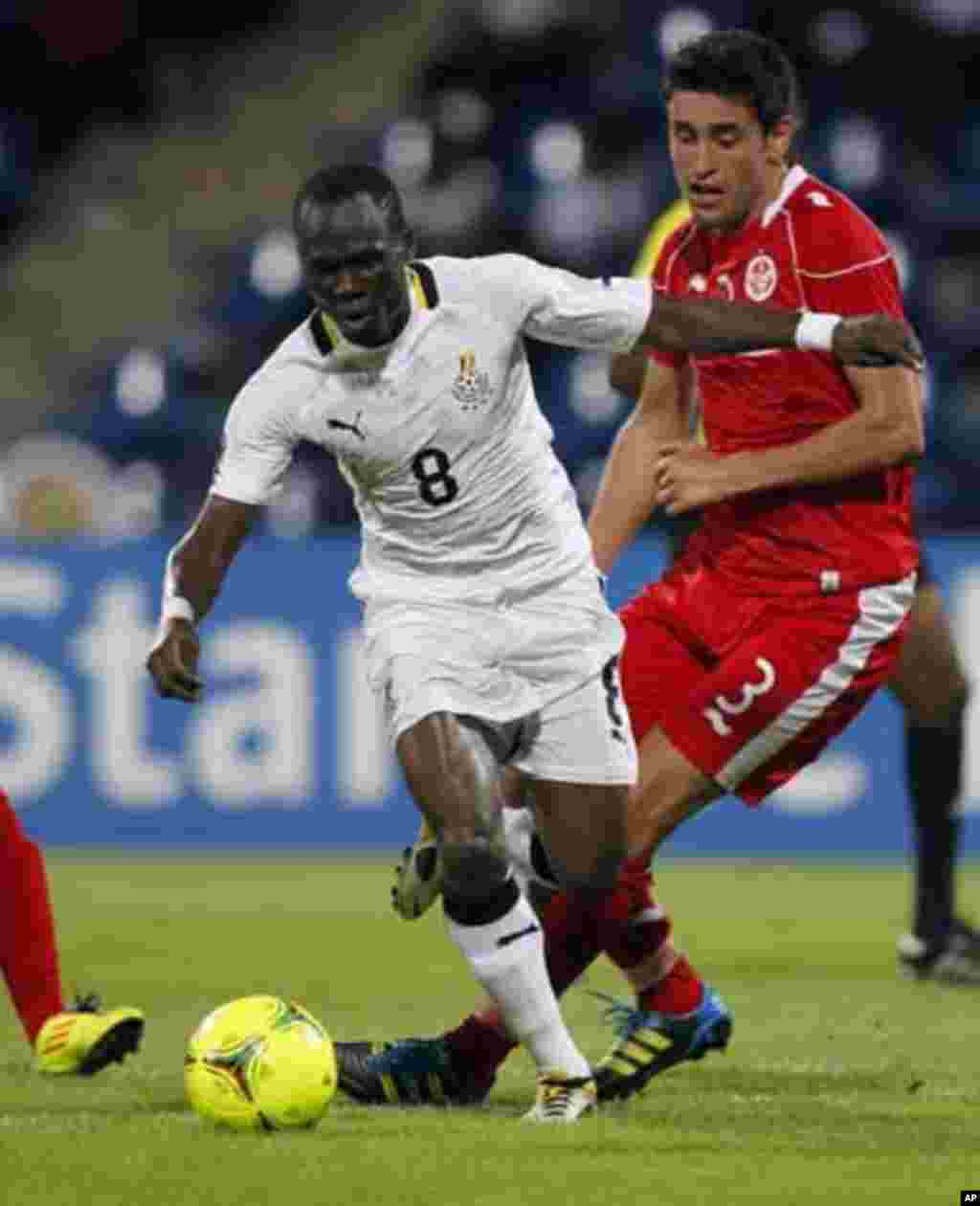Ghana's Emmaneul Badu Agyemang (L) fights for the ball with Tunisia's Karim Haggui during their African Nations Cup quarter-final soccer match at Franceville stadium February 5, 2012.