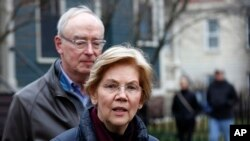 ڈیموکریٹک سینیٹر الزبتھ وارن اپنے شوہر بروس مین کے ہمراہ میڈیا کے نمائندوں سے بات کر رہی ہیں۔