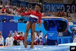 Simone Biles stumbles on the landing after performing on the vault during the artistic gymnastics women's final at the 2020 Summer Olympics, July 27, 2021, in Tokyo.