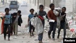 Anak-anak mengumpulkan botol-botol plastik di sebuah jalan di Sanaa, Yaman, 21 November 2019.