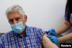 FILE PHOTO: An elderly person receives a dose of the Oxford/AstraZeneca COVID-19 vaccine at Cullimore Chemist, in Edgware, London, Britain, Jan. 14, 2021.