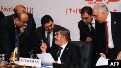 Egyptian President Mohamed Morsi (C) chatting with officials during the closing session of the 12th summit of the Organization of Islamic Cooperation (OIC) in Cairo, February 7, 2013.