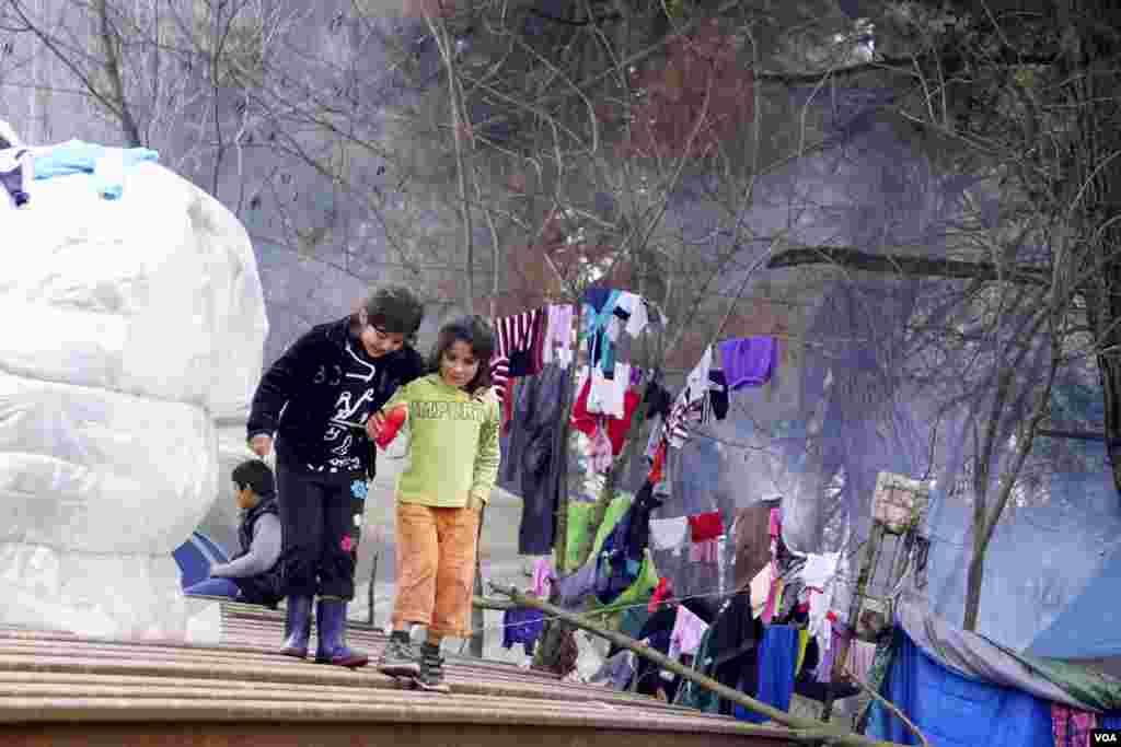 Dua anak pengungsi di kamp Idomeni. (VOA/Jamie Dettmer)