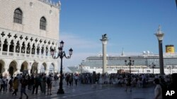 In this file photo, a cruise ship passes by St. Mark's Square in Venice, Italy, Sunday, June 2, 2019. )AP Photo/Luca Bruno)