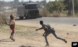 Rioters battle with Zimbabwean police in Harare, Monday, July, 4, 2016.