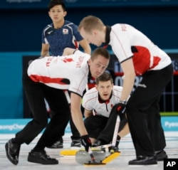 Denmark's skip Rasmus Stjerne, center, makes a call during a men's curling match against Japan at the 2018 Winter Olympics in Gangneung, South Korea, Feb. 20, 2018.