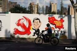 A man rides a bicycle next to a mural showing an image of Chinese President Xi Jinping along a street in Shanghai, China September 28, 2018. REUTERS/Aly Song
