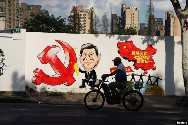 """2018年9月28日,上海一条街上的宣传画,包括习近平的漫画形象、中共党徽和中国地图,还有文字""""民族团结,社会稳定,国家统一"""""""