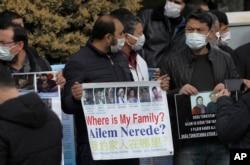 安全人员围住在中国驻安卡拉大使馆外举着失联亲人照片抗议的几十名维吾尔人。(2021年2月9日)