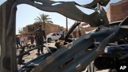 Iraqi security forces inspect the site of a suicide car bomber plowed his vehicle into a checkpoint outside a police building just outside the holy city of Najaf, Iraq, Monday, Aug. 15, 2011.