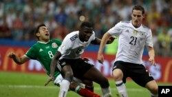 Marco Fabian du Mexique, à gauche, se bat pour récupérer le ballon derrière les Allemands Antonio Ruediger et Sebastian Rudy, à droite, lors du match demi-finale de la Coupe des Confédérations entre l'Allemagne et le Mexique, au Fisht Stadium à Sotchi, Ru