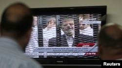 4일 이집트 카이로에서 이집트 시민들이 무함마드 무르시 전 이집트 대통령의 재판에 관한 뉴스를 보고 있다.