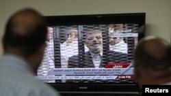 Kahire'de Mursi'nin yarglanmasını televizyonda seyreden Mısırlılar.