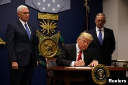FILE - President Donald Trump signs an executive order he said would impose tighter vetting to prevent foreign terrorists from entering the United States at the Pentagon in Washington, Jan. 27, 2017.