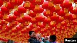 Children play with bubble toy guns under Chinese lunar New Year decorations at a park in Beijing, Jan. 24, 2014.