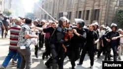 Polisi wanamkamata mfuasi wa rais aliyepinduliwa Misri Mohamed Mursi wakati wa mapambano katikati ya Cairo Ogusati 13, 2013.