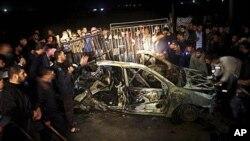 فلسطینی ها در اطراف یک واسطۀ نقلیه جمع شده اند که توسط اسراییلی ها هدف قرار گرفته بود.