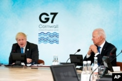 British Prime Minister Boris Johnson speaks as President Joe Biden listens during the G-7 summit at the Carbis Bay Hotel in Carbis Bay, St. Ives, Cornwall, England, June 11, 2021.
