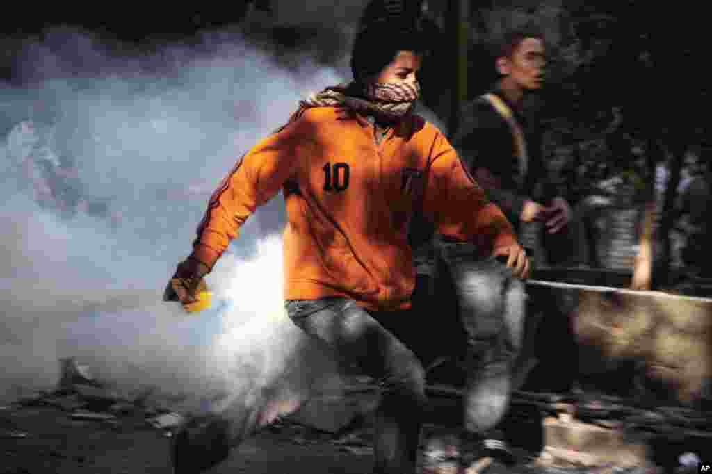 Người biểu tình Ai Cập bỏ chạy trong vụ đụng độ với lực lượng an ninh tại Quảng trường Tahrir ở Cairo, ngày 25 tháng 11, 2012.