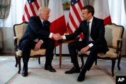 "President Donald Trump shakes hands with French President Emmanuel Macron during a meeting in May. Macron called it ""a moment of truth."""