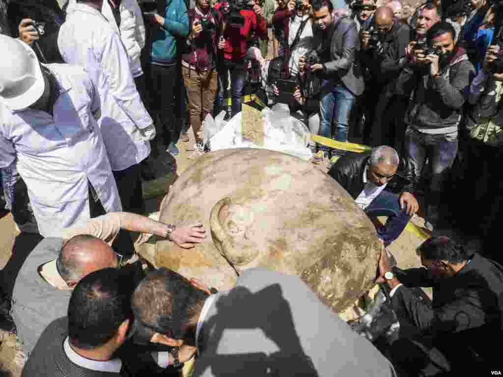 Archaeologists examine the condition of the statue and the writings carved on the back. King Ramses II was famous of stealing other kings monuments and carve his name on it.