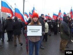 3月1日莫斯科悼念反对派领袖涅姆佐夫的游行中,一名参加者手举标语:(官方)宣传在杀人。(美国之音 白桦拍摄))