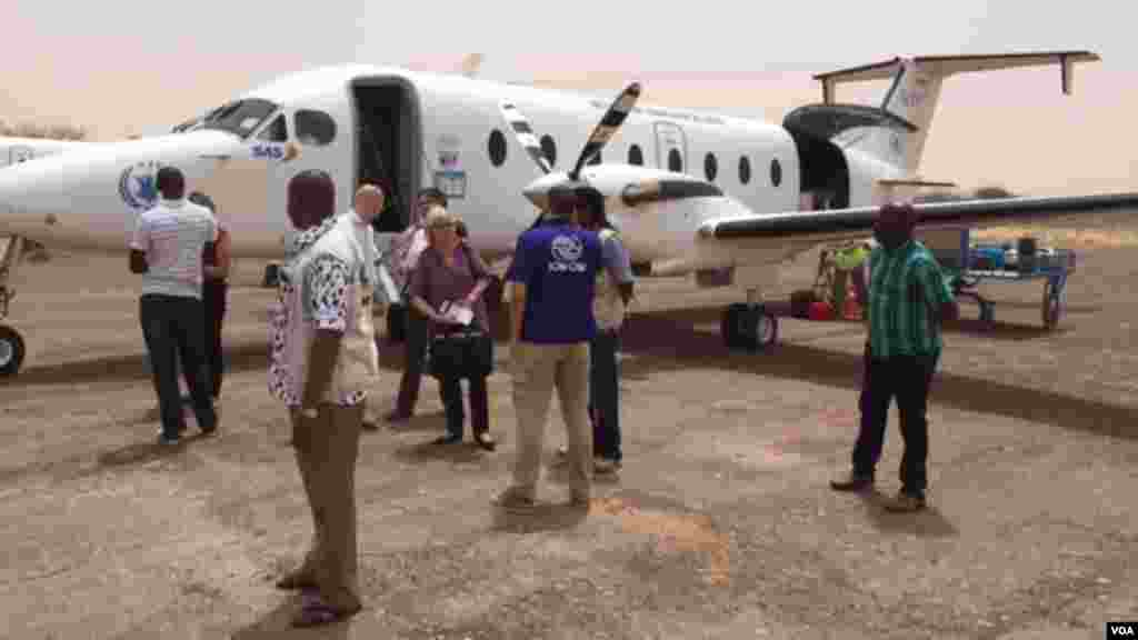 Journalists and aid workers prepare to board a plane at Zinder airport.