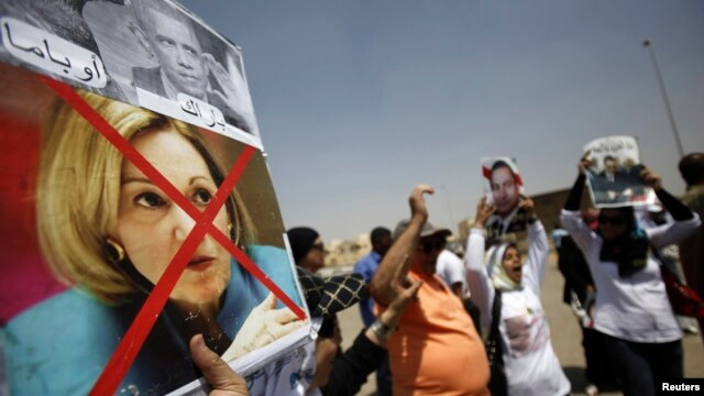 A supporter of Egypt's former President Hosni Mubarak holds a defaced picture of U.S. ambassador to Egypt Anne Patterson (bottom) and U.S. President Barack Obama (top) as others shout slogans against members of the Muslim Brotherhood and supporters of ousted Egyptian President Mohamed Morsi, before Mubarak's trial in Cairo, July 6, 2013.
