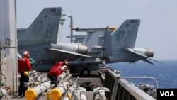 Thủy thủ tàu USS Carl Vinson chuẩn bị gắn rốc kết cho máy bay F-18 trước cuộc tuần tra thường lệ tại Biển Đông ngày 3/3/2017.