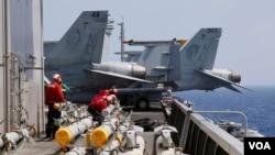 美國海軍卡爾·文森航空母艦上的人員在F-18戰機例行出航前準備為飛機加裝導彈。(2017年3月3日)