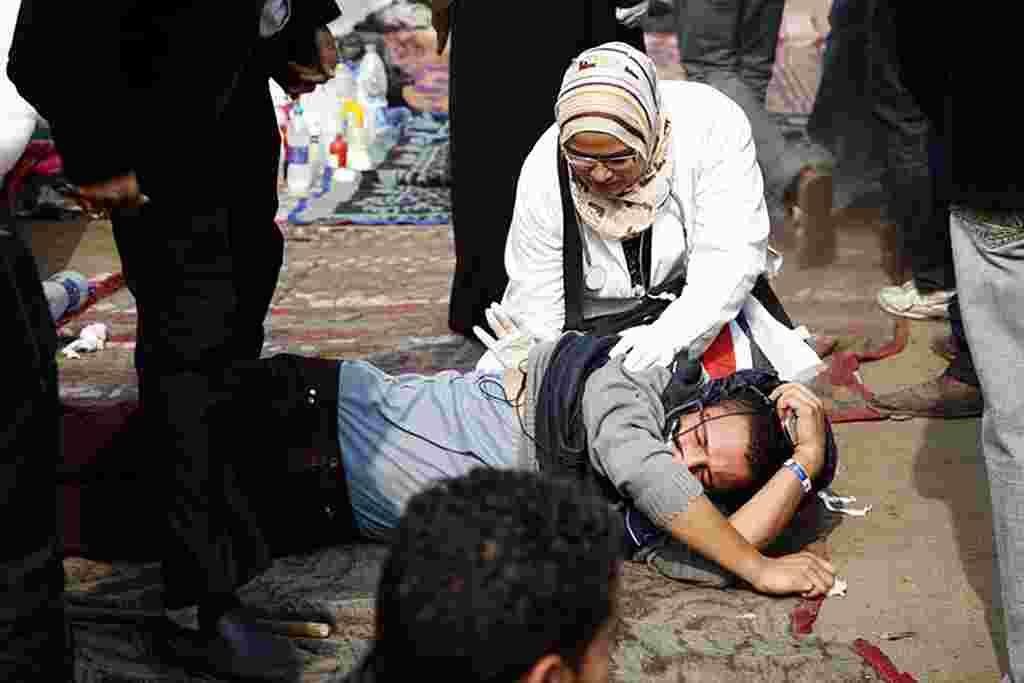 """VOA - Una doctora atienda a uno de los manifestantes heridos durante la marcha, conocida como """"la salvación de Egipto""""."""
