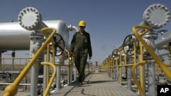 FILE - Iranian oil technician Majid Afshari makes his way to the oil separator facilities in Iran's Azadegan oil field southwest of Tehran, Iran, April 15, 2008.