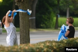Denise Koesterman and Alison Lebrun, right, both of Cincinnati, hang ribbons in honor of Otto Warmbier's homecoming in the Wyoming neighborhood of Cincinnati, Ohio, June 13, 2017.