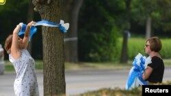 Denise Koesterman ak Alison Lebrun, adwa, tou 2 nan Cincinnati, ap mete riban nan onè retou Otto Warmbier lakay li nan katye Wyoming nan Cincinnati, Ohio, 13 jen, 2017.