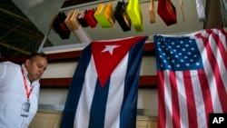 A man walks past Cuban and U.S. flags at the 33rd Havana International Fair (FIHAV) in Havana, Cuba, Nov. 2, 2015.