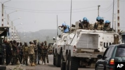 United Nations soldiers talk to forces loyal to Alassane Ouattara as they drive through a republican forces operating base on the outskirts of Abidjan, Ivory Coast, April 9, 2011.