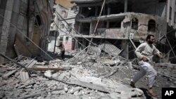 Cư dân đi qua đống đổ nát của căn nhà bị đổ sập sau một vụ không kích của Israel tại thành phố Gaza, ngày 23/4/2014.