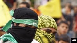 帶著哈馬斯和法塔赫面罩的巴勒斯坦人星期三歡呼簽訂團結協議