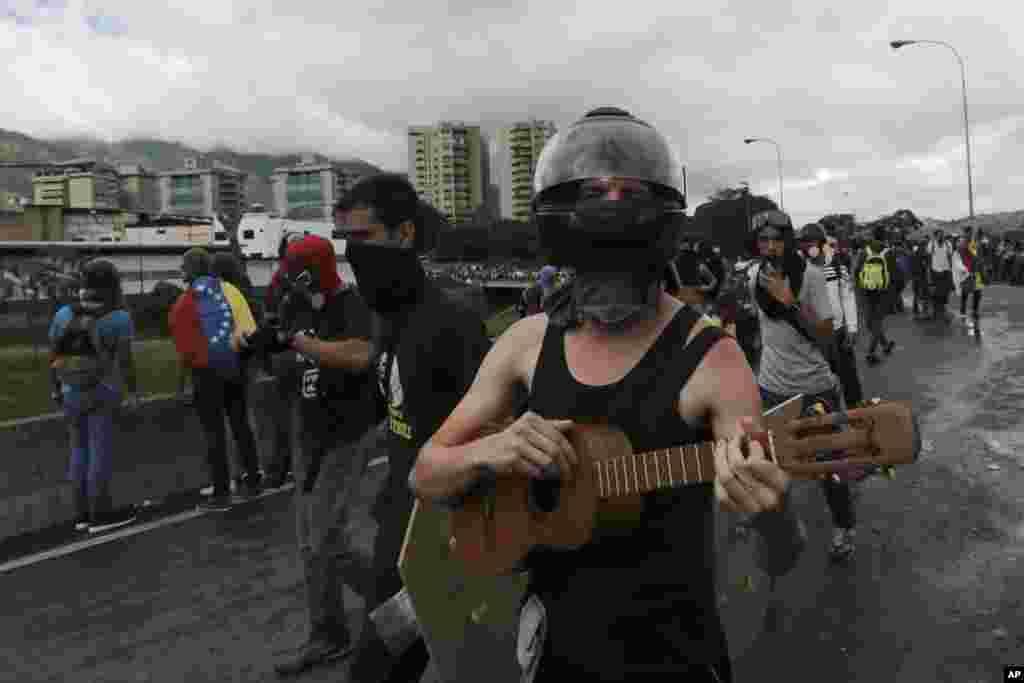 یک معترض در جریان تظاهرات علیه نیکلاس مادور رئیس جمهوری ونزوئلا در حال زدن «کواترو» یک ساز موسیقی سنتی آن کشور است.