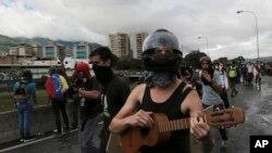 FILE - Anti-government demonstrators protest President Nicolas Maduro along a highway in Caracas, Venezuela, June 19, 2017.