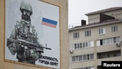 A banner depicting a Russian serviceman is seen on a military barrack building at the base of 247th Air Assault Regiment in the southern city of Stavropol, Russia, Feb. 25, 2016.