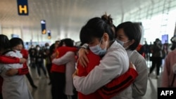 Medical staff from Jilin Province (in red) hug nurses from Wuhan after working together during the COVID-19 coronavirus outbreak during a ceremony before leaving as Tianhe Airport is reopened in Wuhan in China's central Hubei province on April 8, 2020.