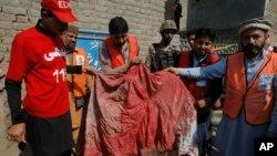 Nhân viên cứu hộ Pakistan cầm trang phục trùm đầu đẫm máu của một phụ nữ bị thiệt mạng trong vụ đánh bom tự sát tại thị trấn Shabqadar, quận Charsadda, ngày 7/3/2016.